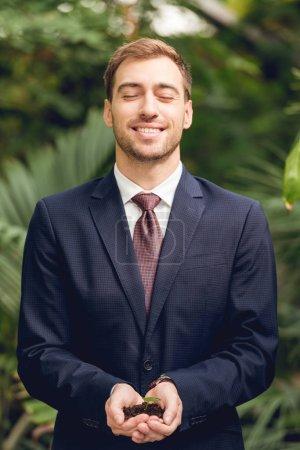 Photo pour Homme d'affaires heureux de sourire avec les yeux fermés dans le procès et la cravate retenant le germe vert et le sol dans des mains dans l'orangerie - image libre de droit