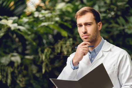 Photo for Pensive scientist in white coat holding journal in green orangery - Royalty Free Image
