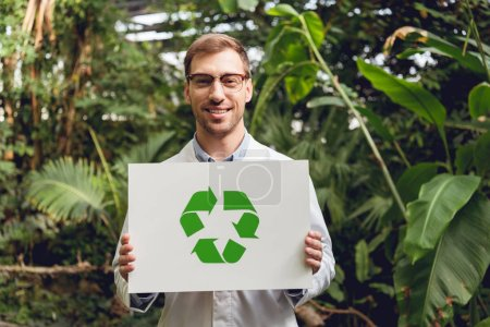 smiling handsome scientist in white coat and glasses holding card with green recycling sign in orangery