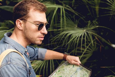Photo pour Handsome tourist in sunglasses holding map in green tropics - image libre de droit