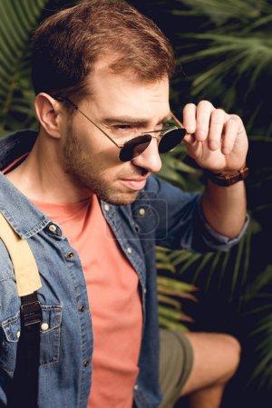 Foto de Apuesto turista tocando gafas de sol en el bosque tropical - Imagen libre de derechos