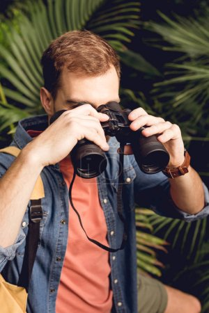 Photo for Handsome tourist looking through binoculars in tropical forest - Royalty Free Image