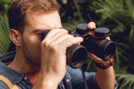 Photo pour Gros plan de touriste regardant par des jumelles dans la forêt tropicale - image libre de droit