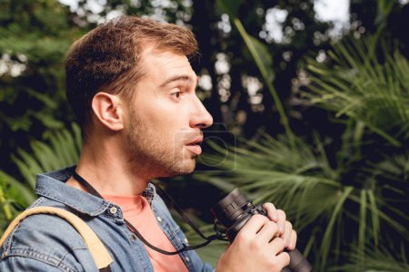Photo for Shocked handsome tourist with binoculars looking away in tropical forest - Royalty Free Image