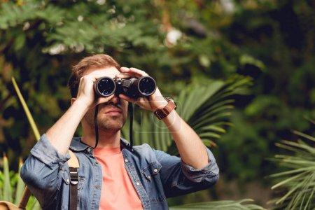 Photo pour Voyageur adulte regardant par des jumelles dans la forêt verte tropicale - image libre de droit