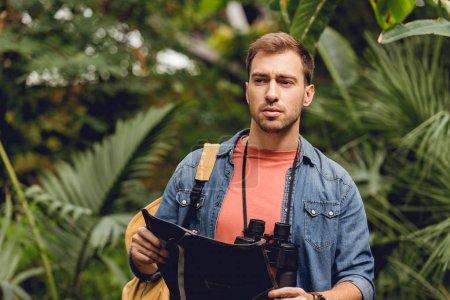 Photo pour Beau voyageur tendu avec des jumelles et sac à dos tenant la carte dans la forêt tropicale verte - image libre de droit