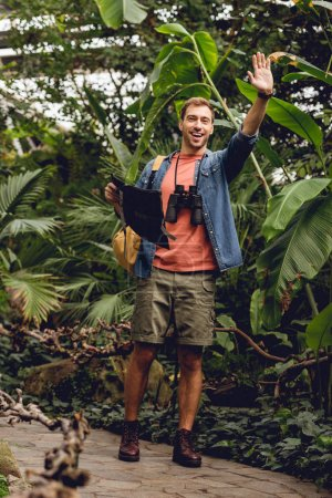 Photo for Handsome happy traveler with binoculars and backpack holding map and waving hand in green tropical forest - Royalty Free Image