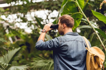 Photo for Adult tourist with backpack looking through binoculars in tropical forest - Royalty Free Image