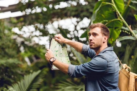Photo pour Beau voyageur avec sac à dos tenant la carte dans la forêt tropicale verte - image libre de droit
