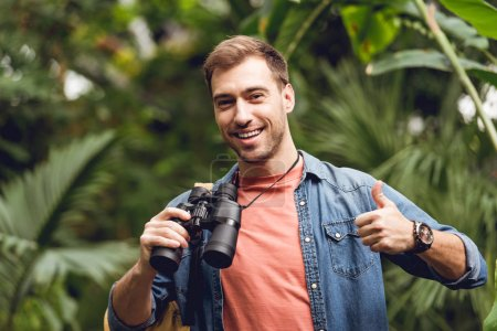 Photo for Handsome happy traveler with binoculars and backpack showing thumb up in green tropical forest - Royalty Free Image