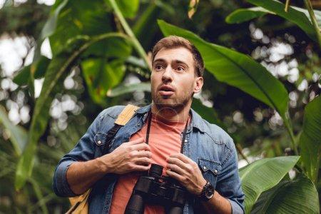 Photo pour Beau voyageur effrayé avec des jumelles et sac à dos dans la forêt tropicale verte - image libre de droit