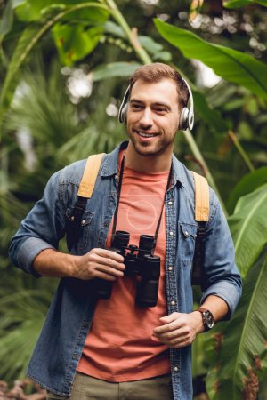 Photo for Happy traveler with backpack and binoculars listening music in headphones in green tropical forest - Royalty Free Image
