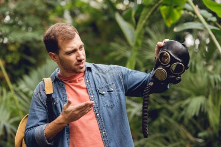 Photo for Confused traveler with backpack pointing at gas mask in tropical forest - Royalty Free Image