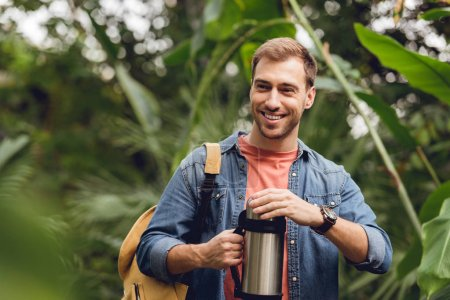 Photo for Selective focus of smiling traveler with backpack opening thermos in tropical forest - Royalty Free Image
