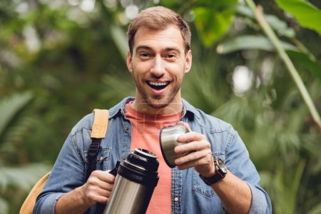 Photo for Happy traveler with backpack opening thermos in tropical forest - Royalty Free Image