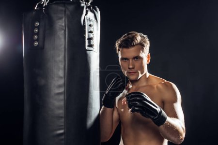 Photo pour Boxeur fort dans des gants restant près du sac de poinçonnage et regardant l'appareil-photo - image libre de droit