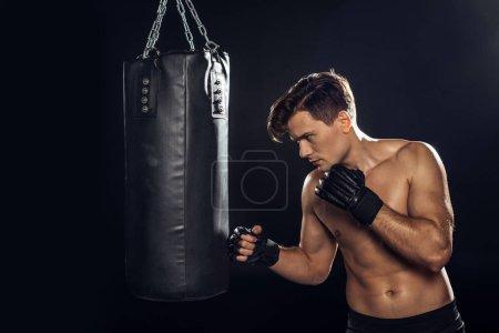 Photo pour Boxeur beau dans la formation de gants de boxe avec le sac de poinçonnage sur le noir - image libre de droit