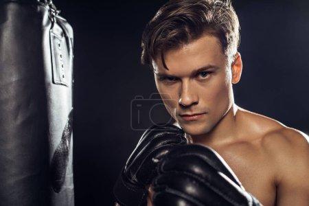Photo pour Boxer restant près de sac de poinçonnage et regardant l'appareil-photo - image libre de droit