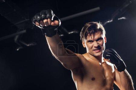 Photo pour Vue à angle bas du boxeur en colère dans des gants détournant les yeux - image libre de droit