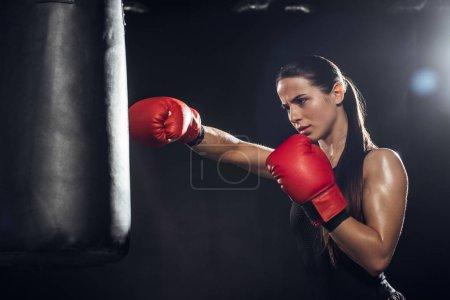 Photo pour Boxeur femelle dans la formation de gants de boxe rouge avec le sac de poinçonnage sur le noir - image libre de droit