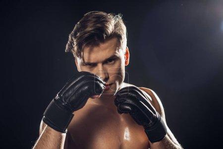 Photo pour Vue de face du boxeur concentré dans des gants regardant l'appareil-photo sur le noir - image libre de droit
