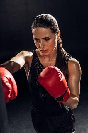 Photo pour Vue de grand angle de boxeur fatigué dans la formation de gants de boxe rouge avec le sac de poinçonnage sur le noir - image libre de droit
