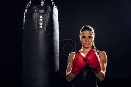 Photo pour Vue de face du boxeur dans les gants de boxe rouge restant près du sac de poinçonnage sur le noir - image libre de droit