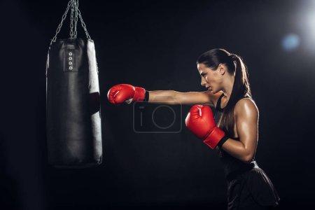 Photo pour Vue latérale de boxeur femelle dans la formation de gants de boxe rouge avec le sac de poinçonnage - image libre de droit