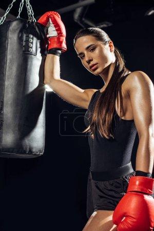 Photo pour Boxeur femelle dans les gants de boxe rouge restant près de sac de poinçonnage - image libre de droit