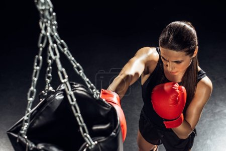 High angle view of boxer in red boxing gloves training with punching bag
