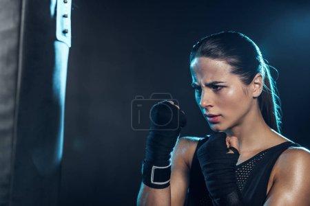 Photo pour Boxeur épuisé dans des gants regardant le sac de poinçonnage sur le noir - image libre de droit