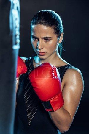 Photo pour Boxeur épuisé en gants rouges regardant le sac de poinçonnage sur le noir - image libre de droit