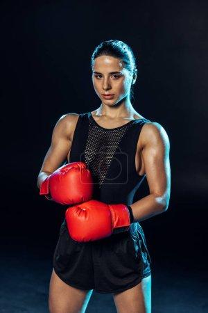 Photo pour Boxeur fort dans les gants rouges regardant l'appareil-photo sur le noir - image libre de droit