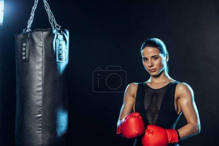 Photo pour Boxeur fort en gants rouges se tenant près du sac de poinçonnage et regardant l'appareil-photo sur le noir - image libre de droit