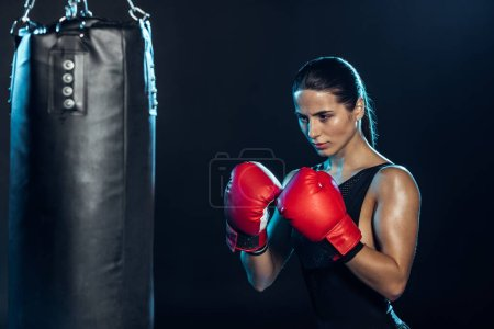 Photo pour Boxeur confiant dans des gants rouges regardant le sac de poinçonnage sur le noir - image libre de droit