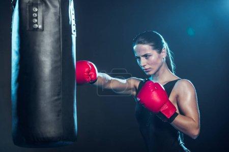 Photo pour Boxeur fatigué dans la formation de gants de boxe rouge avec le sac de poinçonnage sur le noir - image libre de droit