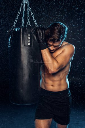 Photo for Exhausted boxer in black briefs holding punching bag and looking down on black - Royalty Free Image