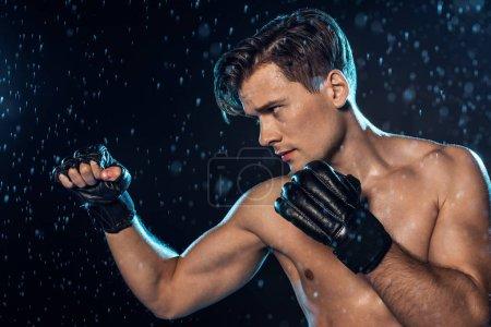 Photo pour Formation de boxeur concentrée sous les gouttes d'eau et regardant loin sur le noir - image libre de droit