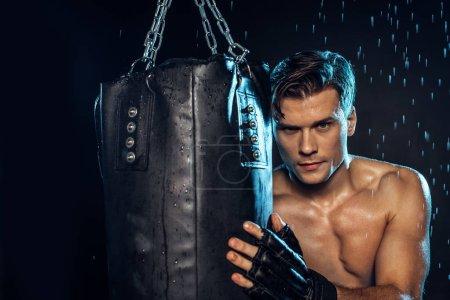 Photo pour Boxer retenant le sac de poinçonnage et regardant l'appareil-photo sur le noir - image libre de droit