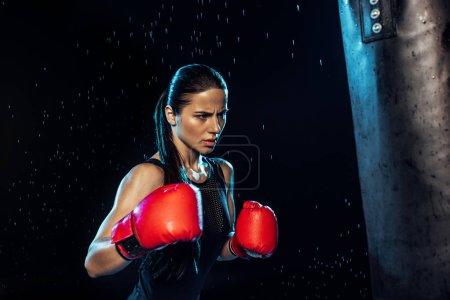 Photo pour Boxeur pensive dans la formation de gants de boxe rouge sous des gouttes d'eau sur le noir - image libre de droit