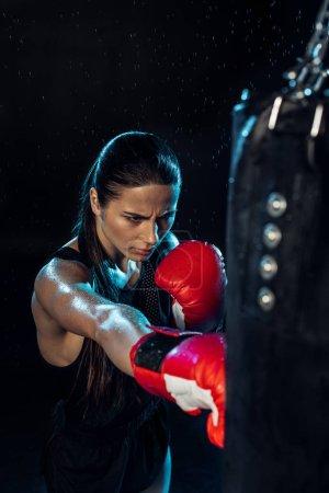 Photo pour Vue de grand angle de boxeur pensive dans la formation de gants de boxe rouge sous des gouttes d'eau sur le noir - image libre de droit