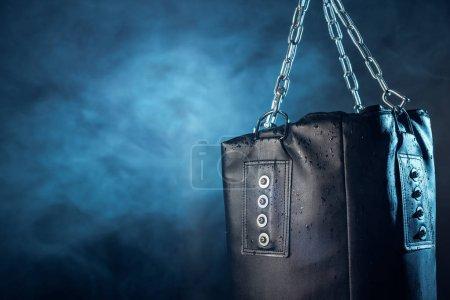 Photo pour Sac de poinçonnage en cuir suspendu sur les chaînes en acier sur l'obscurité - image libre de droit