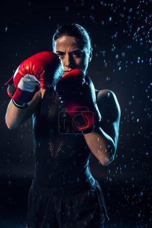 Photo pour Boxer concentré en gants de boxe rouge debout sous des gouttes d'eau sur fond noir - image libre de droit