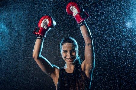 Photo pour Boxeur souriant dans les gants de boxe rouge montrant Oui geste sous l'eau tombe sur le noir - image libre de droit