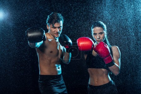 Photo for Two boxers in boxing gloves standing under water drops and looking at camera - Royalty Free Image