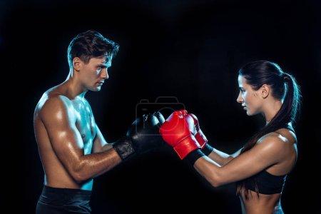 Photo pour Vue latérale de deux boxeurs en gants de boxe s'entraînant ensemble isolés sur noir - image libre de droit
