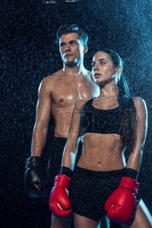 Photo pour Deux boxeurs dans des gants de boxe debout sous des gouttes d'eau et regardant loin sur noir - image libre de droit