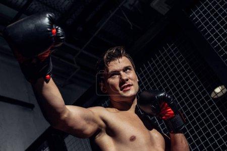 Photo pour Vue de bas angle du boxeur dans la formation de gants de boxe et regardant loin - image libre de droit