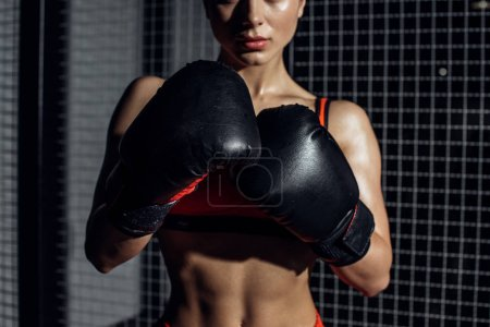Photo for Cropped view of muscular woman in black boxing gloves - Royalty Free Image