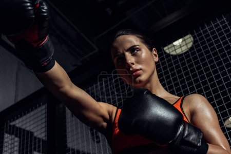Photo for Low angle view of boxer in boxing gloves training and looking away - Royalty Free Image